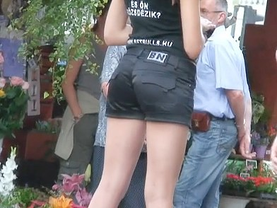 Frisky girl in cowboy hat and sexy shorts is teasingly waving ass cheeks in the street